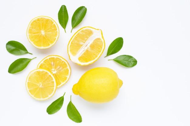 Limón y rodajas con hojas aisladas en blanco