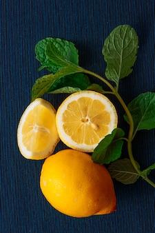 Un limón con rodajas con hojas verdes vista de ángulo alto sobre un fondo mantel azul oscuro