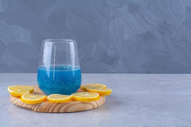 Limón en rodajas junto a un vaso de batido azul sobre una placa de madera, sobre la mesa de mármol.