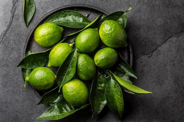 Limón verde con hojas frescas en un plato negro, fondo de pizarra