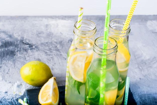 Limonada en botellas con hielo y menta.