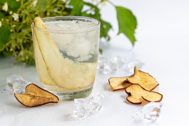 Limonada casera con hielo y peras en rodajas en un vaso sobre un fondo claro