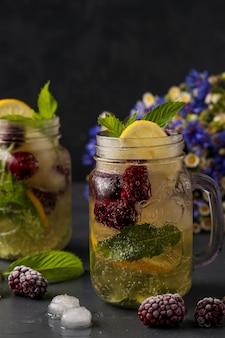 Limonada casera con limón, mora y menta en vidrio sobre un fondo oscuro