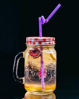 Limonada dentro de un frasco con tubo violeta.