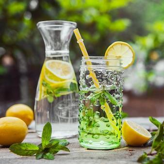 Limonada e ingredientes en jarra de vidrio y tarro en la mesa de madera y jardín, primer plano.