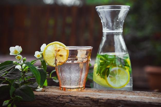 Limonada con flores en rama en vidrio y jarra en mesa de madera y patio, vista lateral.