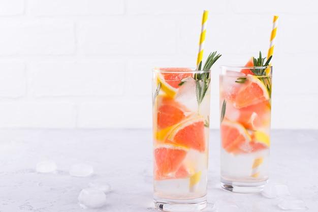 Limonada fresca fría casera con hielo de pomelo y hierbas de romero. receta de agua de soda desintoxicante