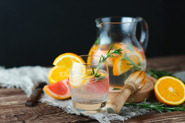 Limonada fresca de verano con pomelo y romero en una vieja mesa de madera. concepto de verano