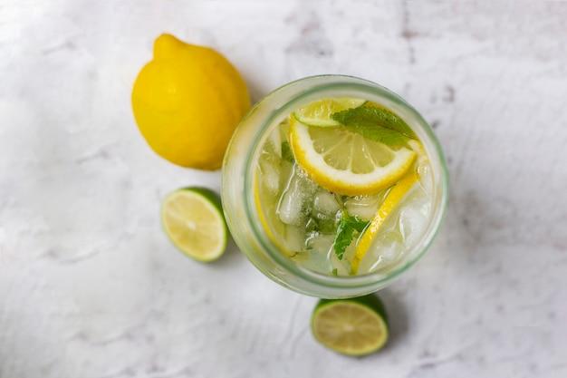 Limonada fría con limón, lima y menta en vaso