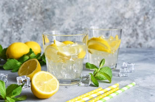 Limonada fría con limón, menta y hielo sobre un fondo de hormigón.