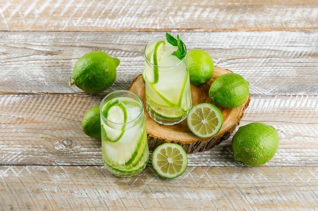 Limonada helada en vasos con limón, albahaca plana sobre madera y tabla de cortar