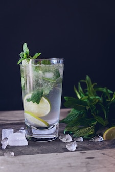 Limonada de hielo con limón en un vaso de vidrio sobre un negro