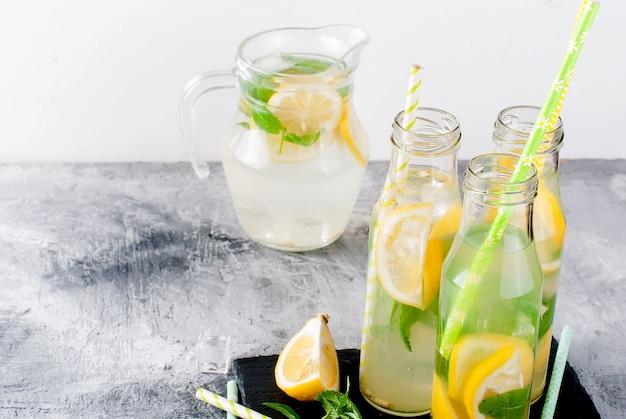 Limonada en jarra de vidrio y botellas con hielo y menta