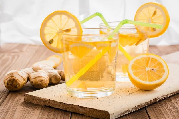 Limonada con limón y jengibre en vasos transparentes sobre una mesa de madera