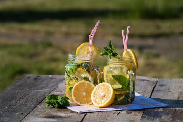 Limonada con limón, menta y hielo, en copas, sobre mesa de madera vieja, al aire libre.
