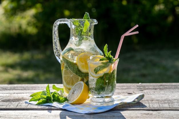 Limonada con limón, menta y hielo, en una jarra y un frasco, sobre una mesa de madera vieja, al aire libre.