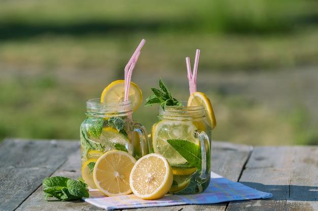 Limonada con limón, menta y hielo, en una jarra y un frasco sobre una mesa de madera vieja