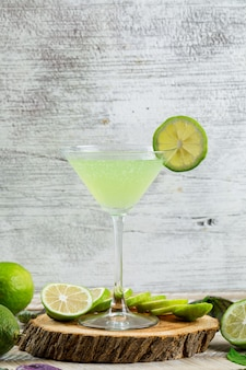 Limonada con limones, hojas, tabla de cortar en un vaso de madera y sucio,