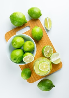 Limonada con limones en un vaso en blanco y tabla de cortar, vista superior.