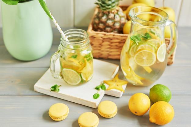 Limonada, macarons dulces, frutas y florero