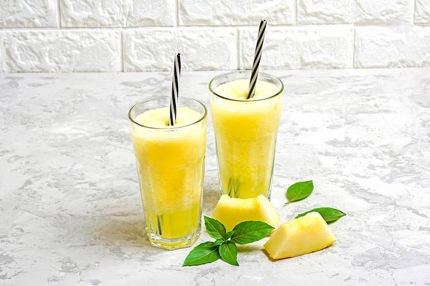 Limonada de melón, batido con hielo y albahaca en un vaso sobre la mesa gris. bebida refrescante y desintoxicante de verano estilo rústico