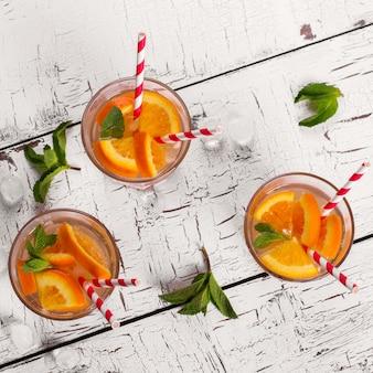 Limonada con naranja, soda y menta en mesa de madera blanca, vista superior