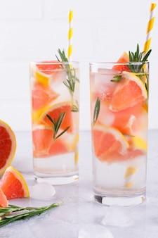 Limonada de pomelo. dos vasos de bebida refrescante, agua con pomelo, ramas de romero y hielo. concepto de receta, cóctel