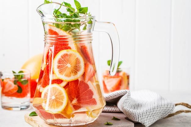 Limonada de pomelo con limón y menta en jarra de vidrio.