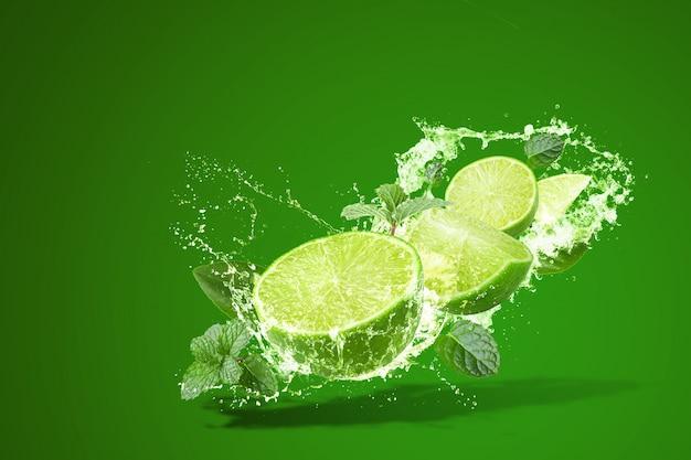 Limonada que salpica en la fruta verde del limón aislada en verde