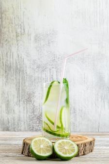 Limonada en un vaso con limón, albahaca, vista lateral de tabla de cortar en madera y sucio