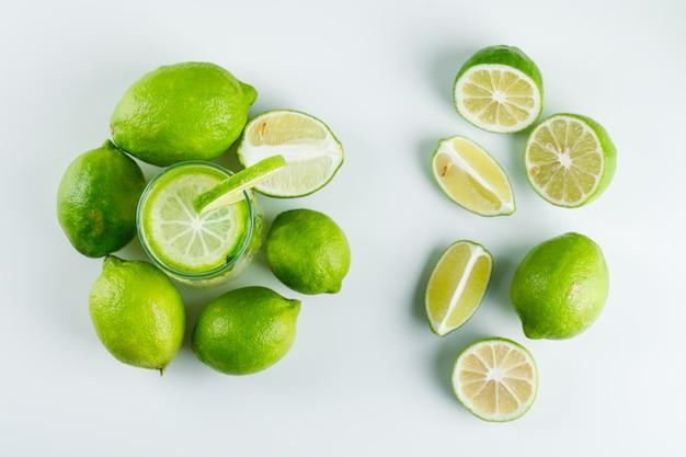 Limonada en un vaso con limones, hierbas, paja vista superior sobre un blanco