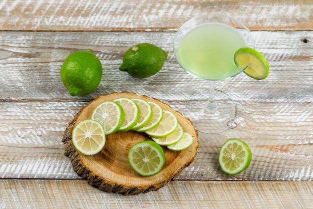 Limonada en un vaso con limones planos sobre madera y tabla de cortar