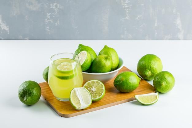 Limonada en un vaso con limones, tabla de cortar vista de ángulo alto en blanco y yeso