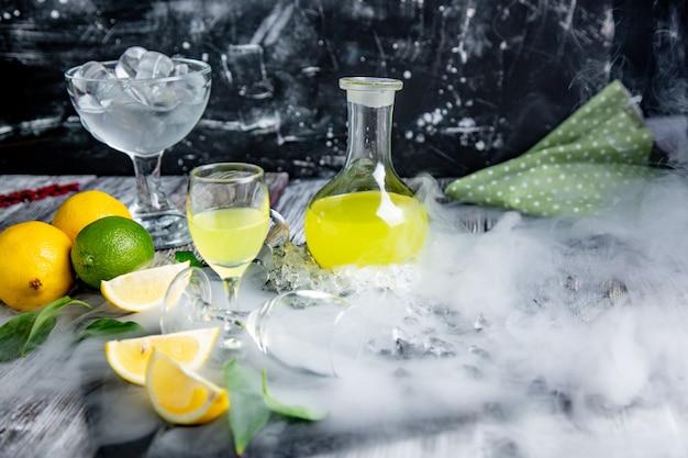 Limoncello digestivo típico italiano con limones frescos en humo, enfoque selectivo