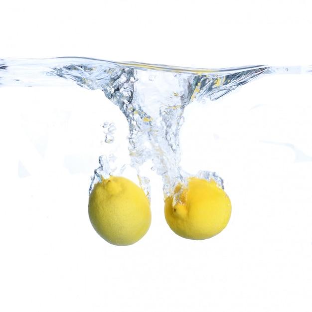Limones en el agua con burbujas y salpicaduras. de cerca. aislado en blanco concepto e idea con limones