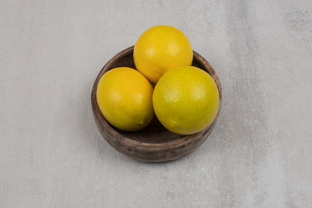Limones amargos frescos en un tazón de madera.