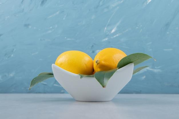 Limones amarillos frescos en la placa blanca.
