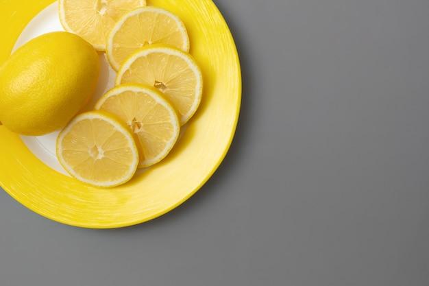 Limones amarillos en placa amarilla en superficie gris final. colores del año 2021. illuminating y ultimate grey. endecha plana.