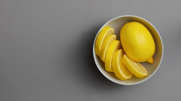 Limones amarillos en placa gris sobre superficie gris final. colores del año 2021. illuminating y ultimate grey. endecha plana.