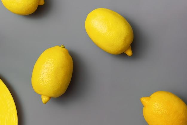 Limones amarillos sobre la superficie gris definitiva. colores del año 2021. illuminating y ultimate grey. endecha plana