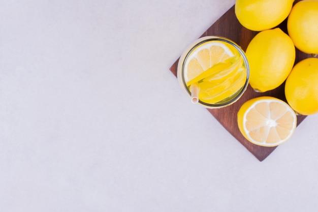 Limones amarillos con un vaso de limonada.