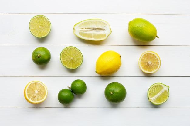 Limones y cales maduros sobre madera blanca.