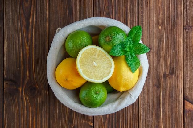 Limones en una canasta sobre una superficie de madera. vista superior.