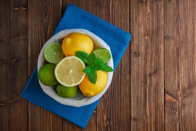 Limones en una canasta con vista superior de tela azul sobre una superficie de madera