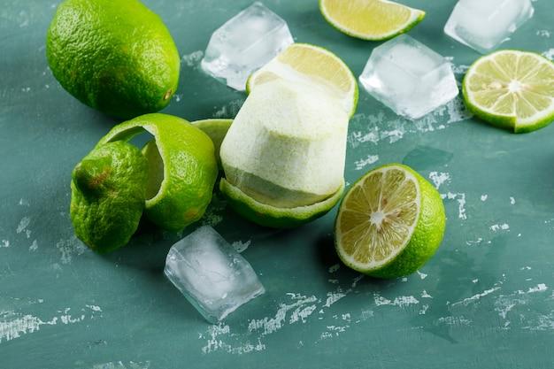 Limones con cáscara, cubitos de hielo en yeso, vista de ángulo alto.