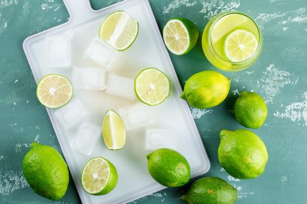 Limones con cubitos de hielo, limonada plana sobre yeso y tabla de cortar