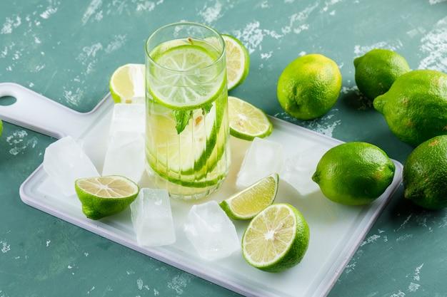 Limones con cubitos de hielo, limonada vista de ángulo alto en yeso y tabla de cortar