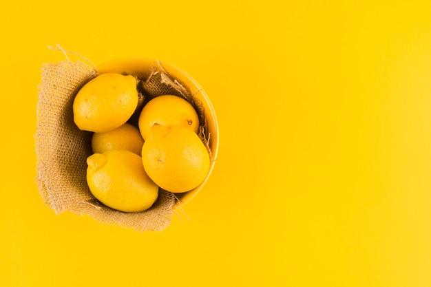 Limones enteros en el recipiente con tela de yute sobre fondo amarillo