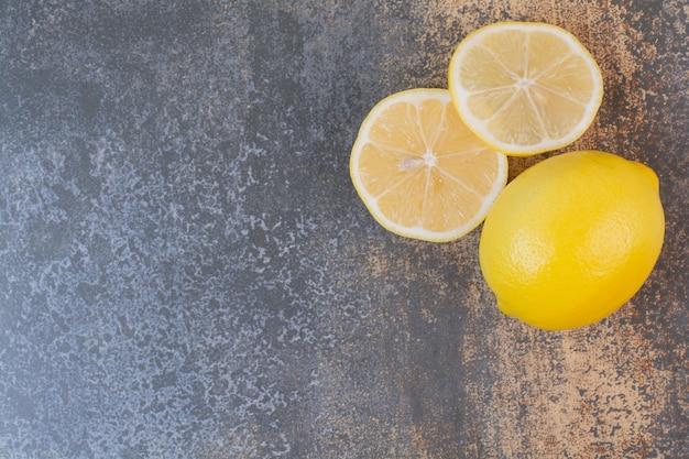 Un limones enteros con rodajas en el espacio de mármol.