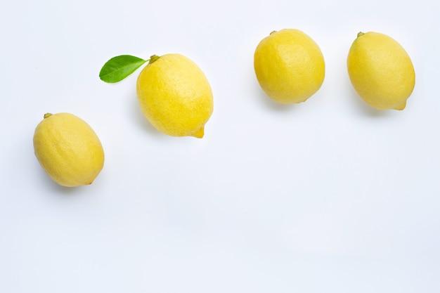 Limones frescos con hoja verde sobre fondo blanco.